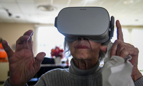 A nursing-home resident wearing a virtual reality headset.